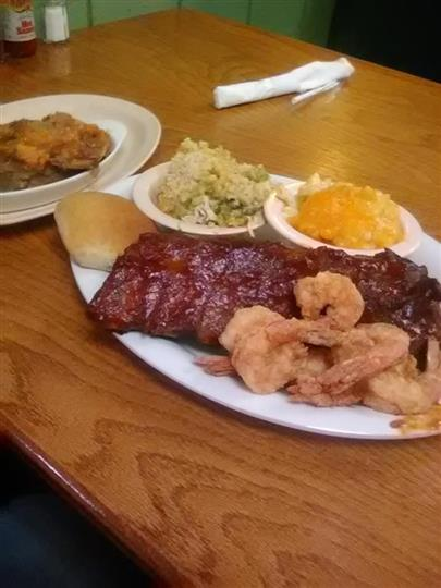 BBQ ribs served with fried shrimp and sides of macaroni and cheese and coleslaw with a bun on the side