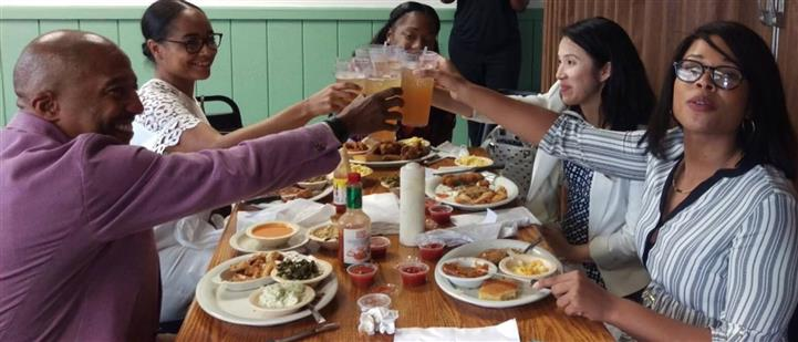 People raising their glasses while enjoying a meal around the table