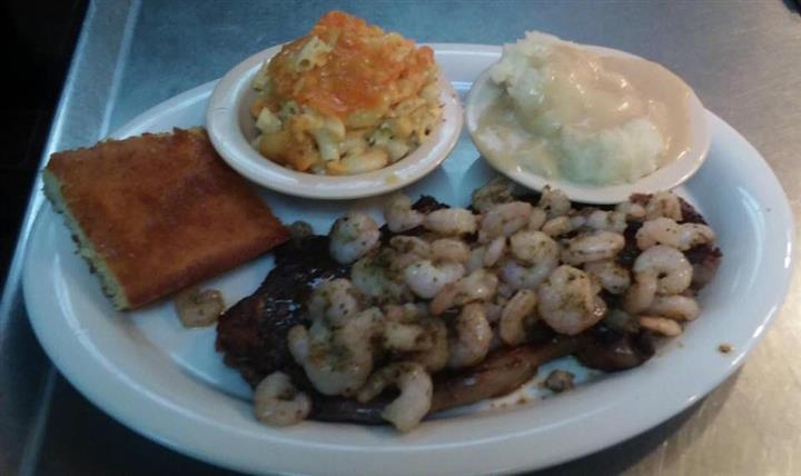 Steak topped with shrimp served with macaoni and cheese and mashed potatoes with cornbread