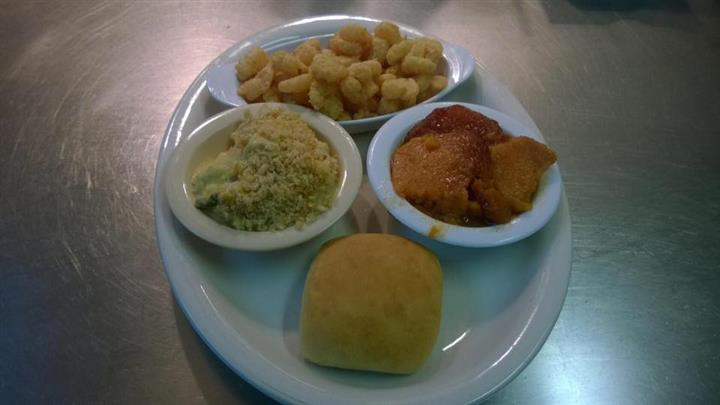 Popcorn shrimp served with side dishes and a bun on the side