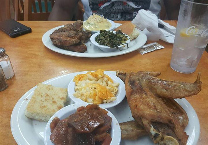 Two big plates of meat and side dishes on a table top served for a meal