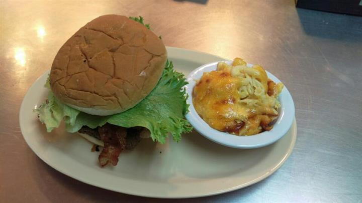 Burger with bacon and lettuce served with a side of macaroni and cheese