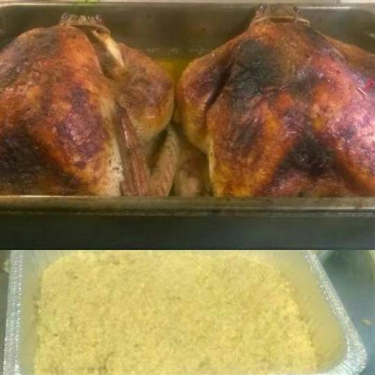Two whole roasted chickens on a food display with a tin of rice underneath