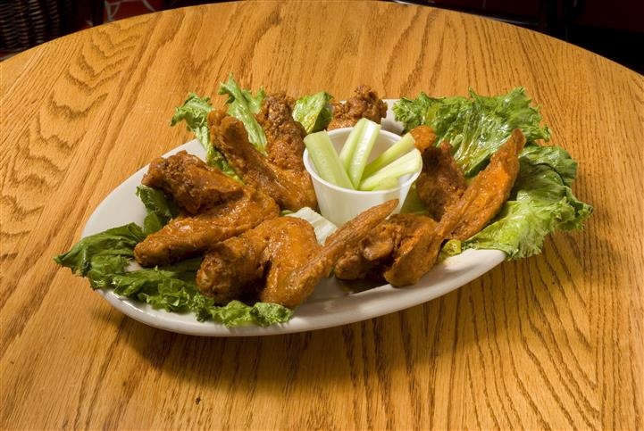 Chicken wings served on a platter over a bed of lettuce and served with cucumbers