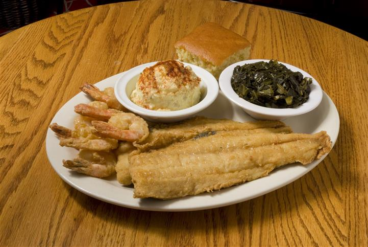 Fish filet with fried shrimp served with side dishes and cornbread
