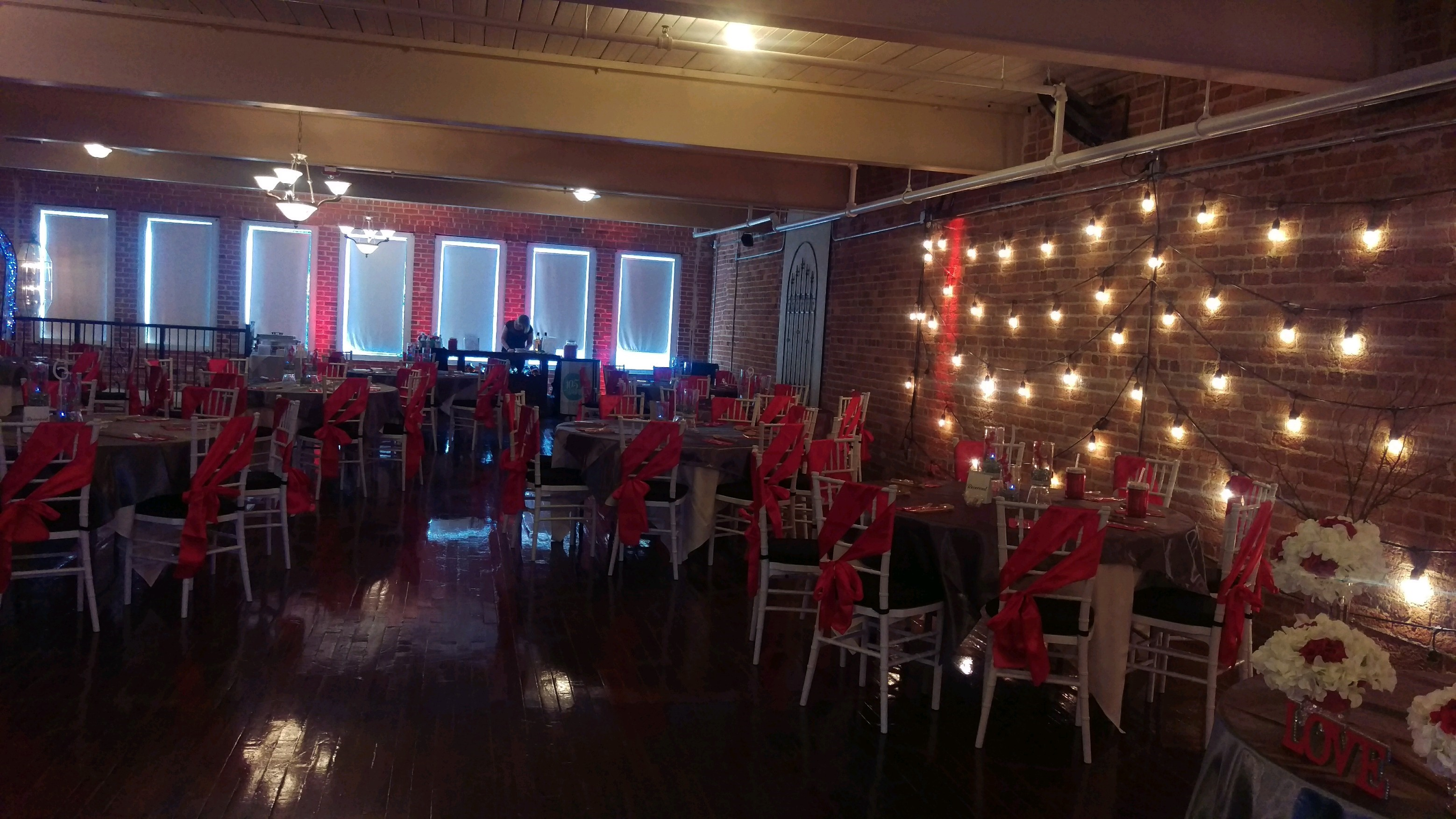 Restaurant hall with round tables decorated with red sashes and string lights on a brick wall