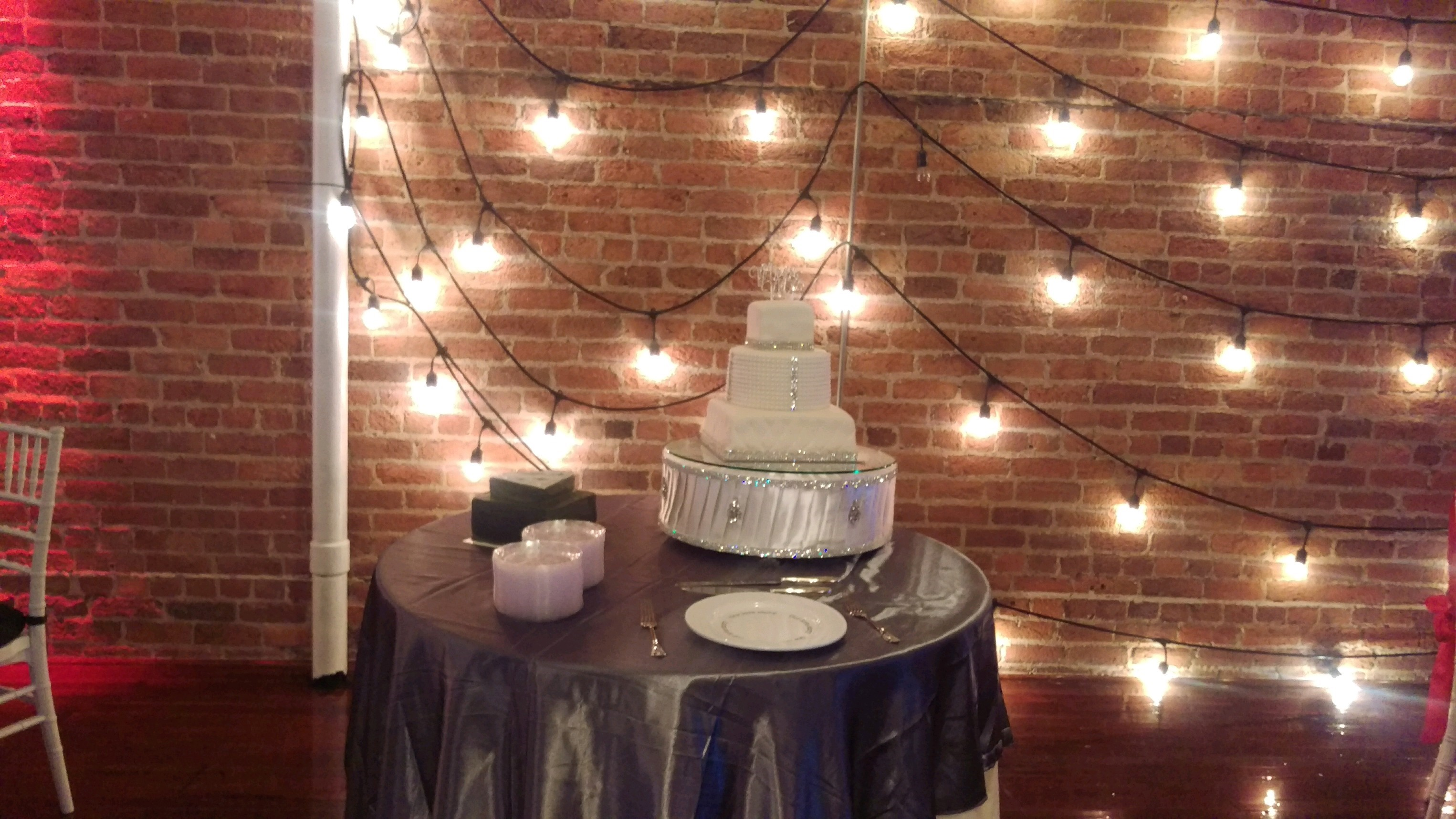 Round table with a decorated white cake on top and stacks of dessert plates on the side by a brick wall with string lights