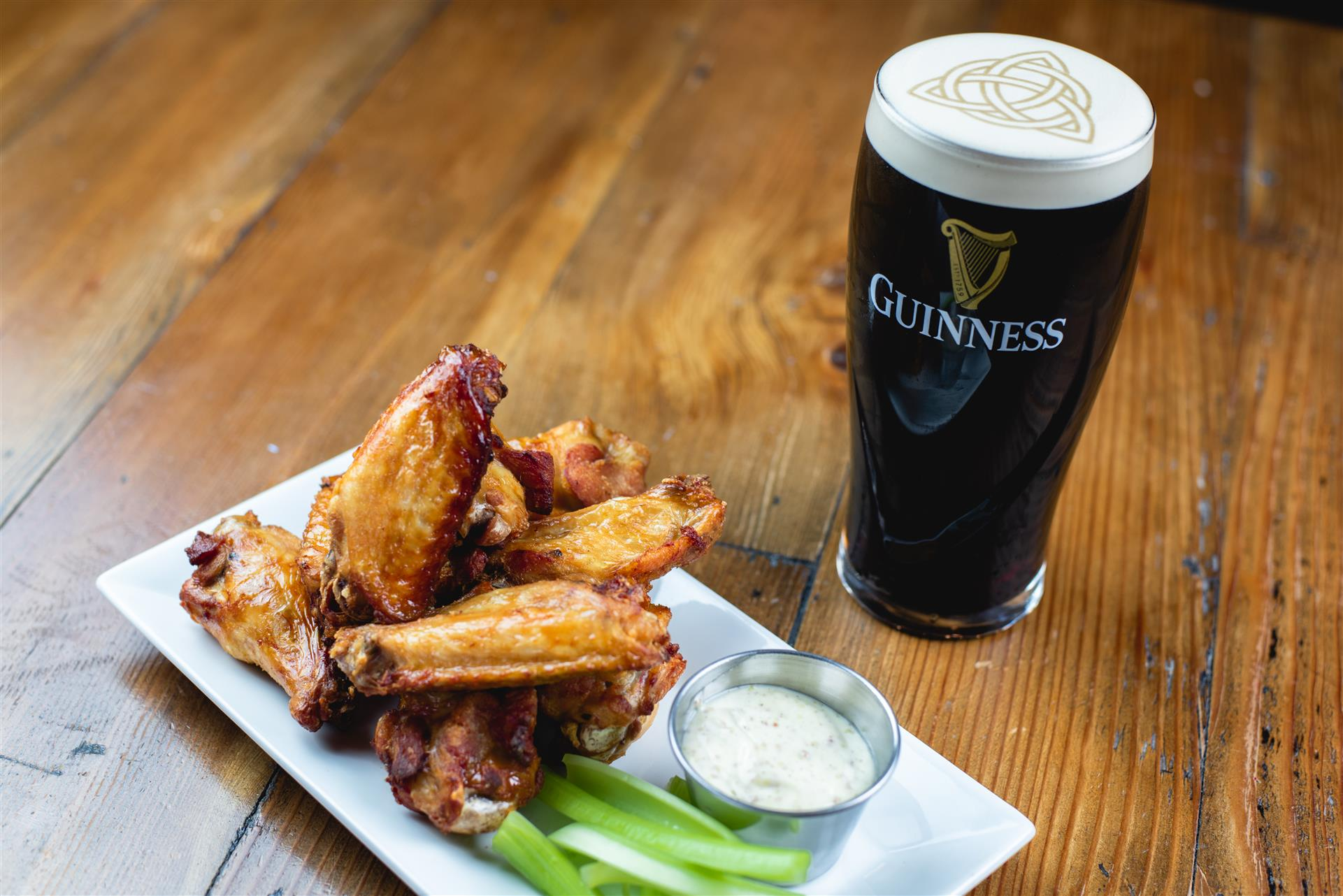 Buffalo wings with a side of celery and ranch with a Guinness Pint