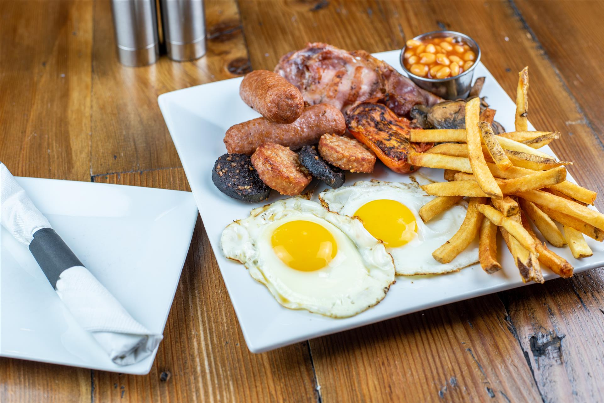 A plate with two eggs. sausage, baked beans and french fries