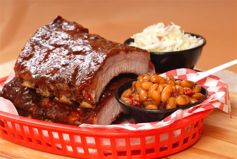 a basket with two bbq ribs, a side of baked beans and a side of coleslaw