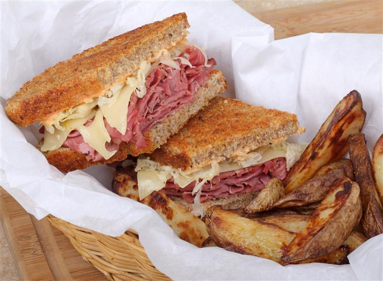 a basket containing a reuben sandwich and a side of potato wedges