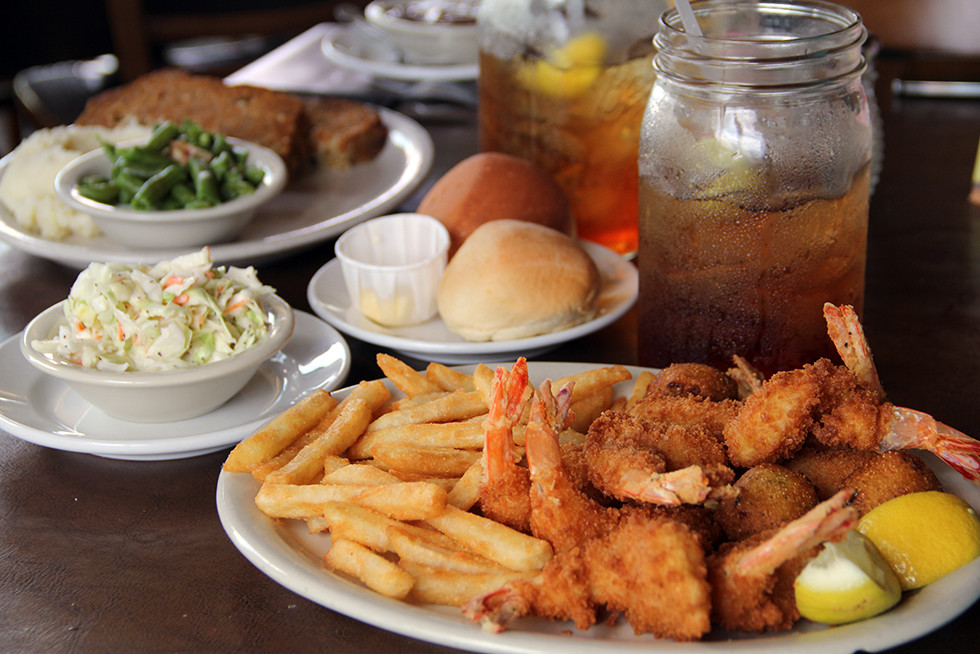 plate with fried shrimp, french fries, side of coleslaw with rolls and butter and sweet tea