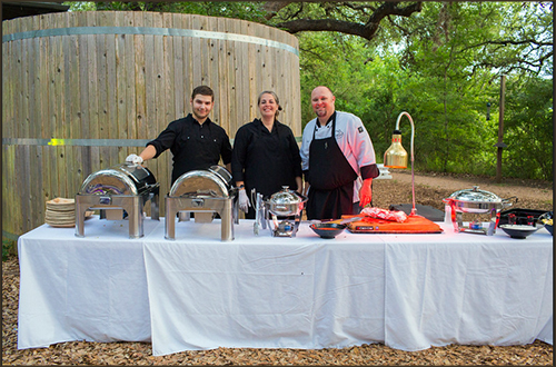 three employees standing behind catering table
