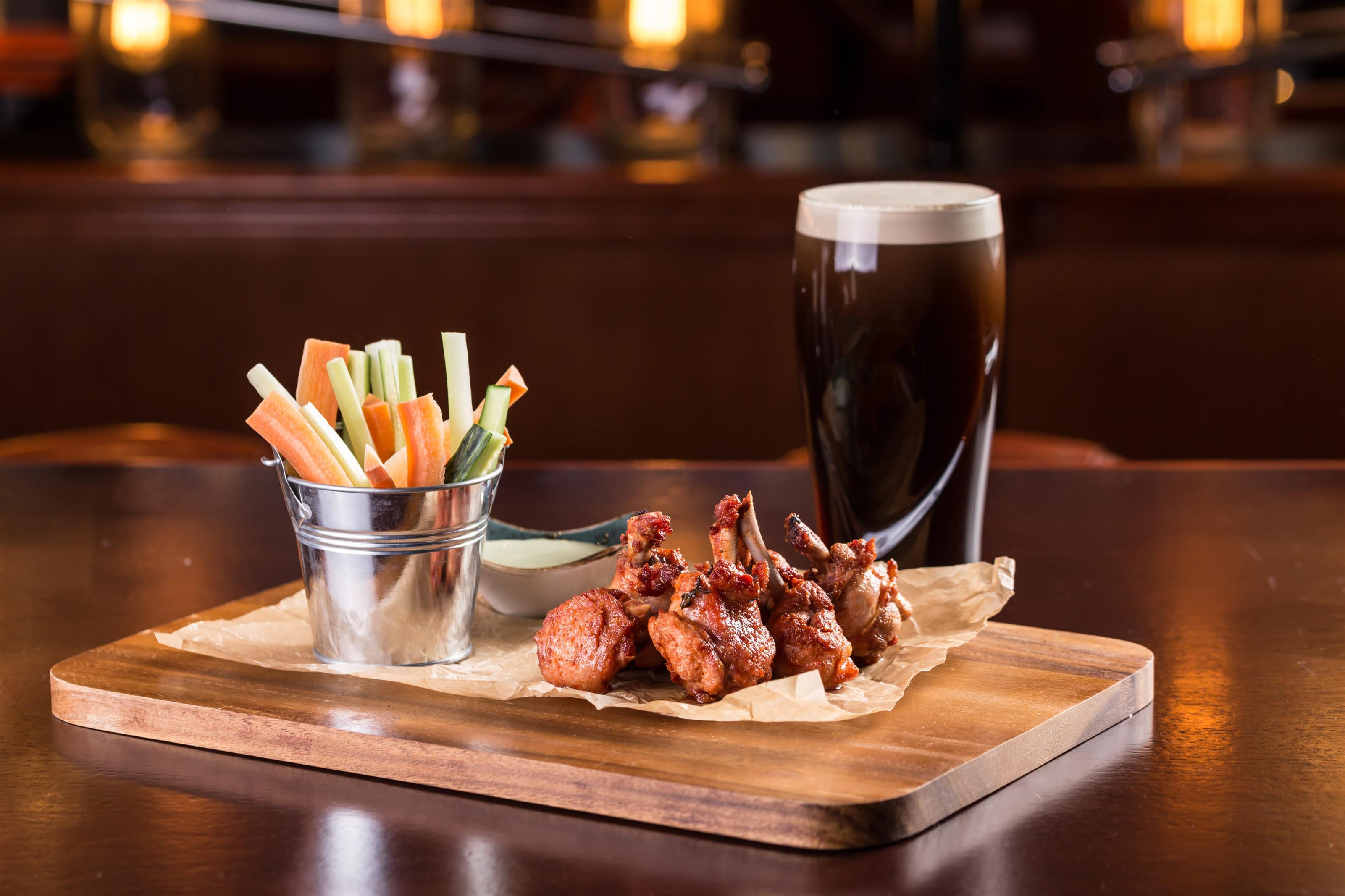 a tray of chicken wings with a side of carrots and celery with a pint of dark beer
