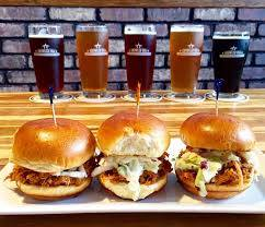 Glasses of beer lined up in the background. Three chicken sandwiches on a plate in the front