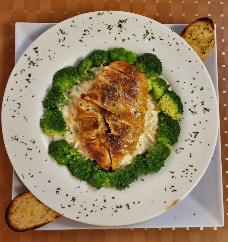 Grilled chicken over pasta and alfredo sauce surrounded by broccoli and garlic bread