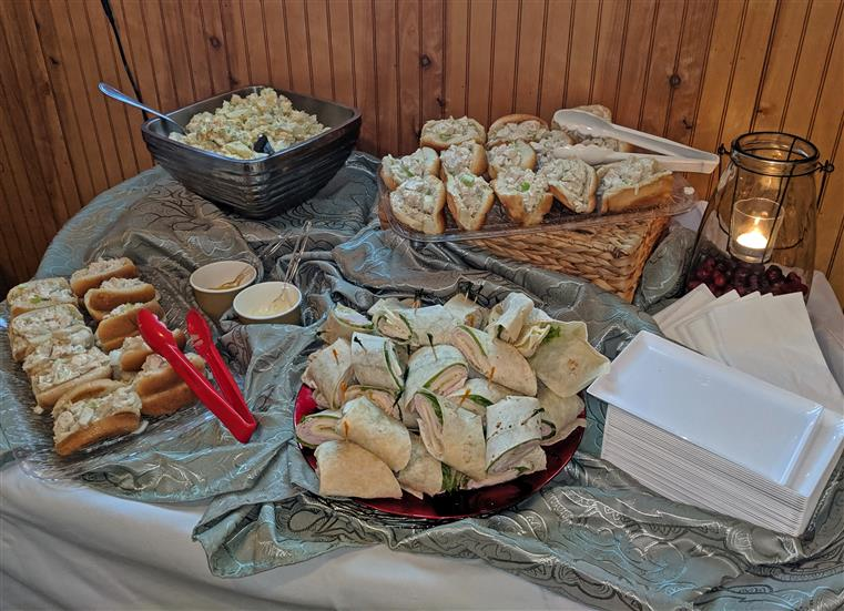 A buffet table with pre-made wraps, sandwiches, and potato salad.