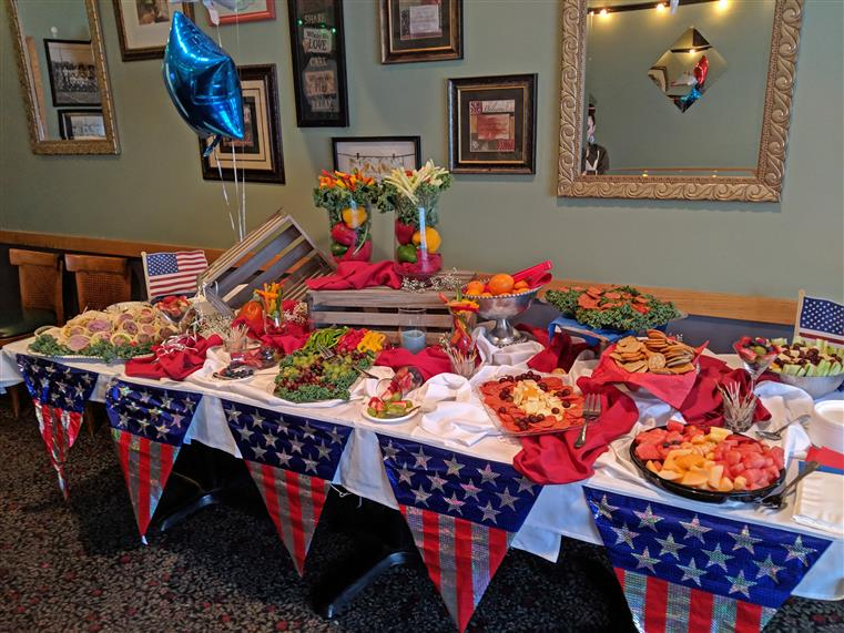 Buffet table set for an american themed event. Charcuterie boards and american flag decorations are covering the table.