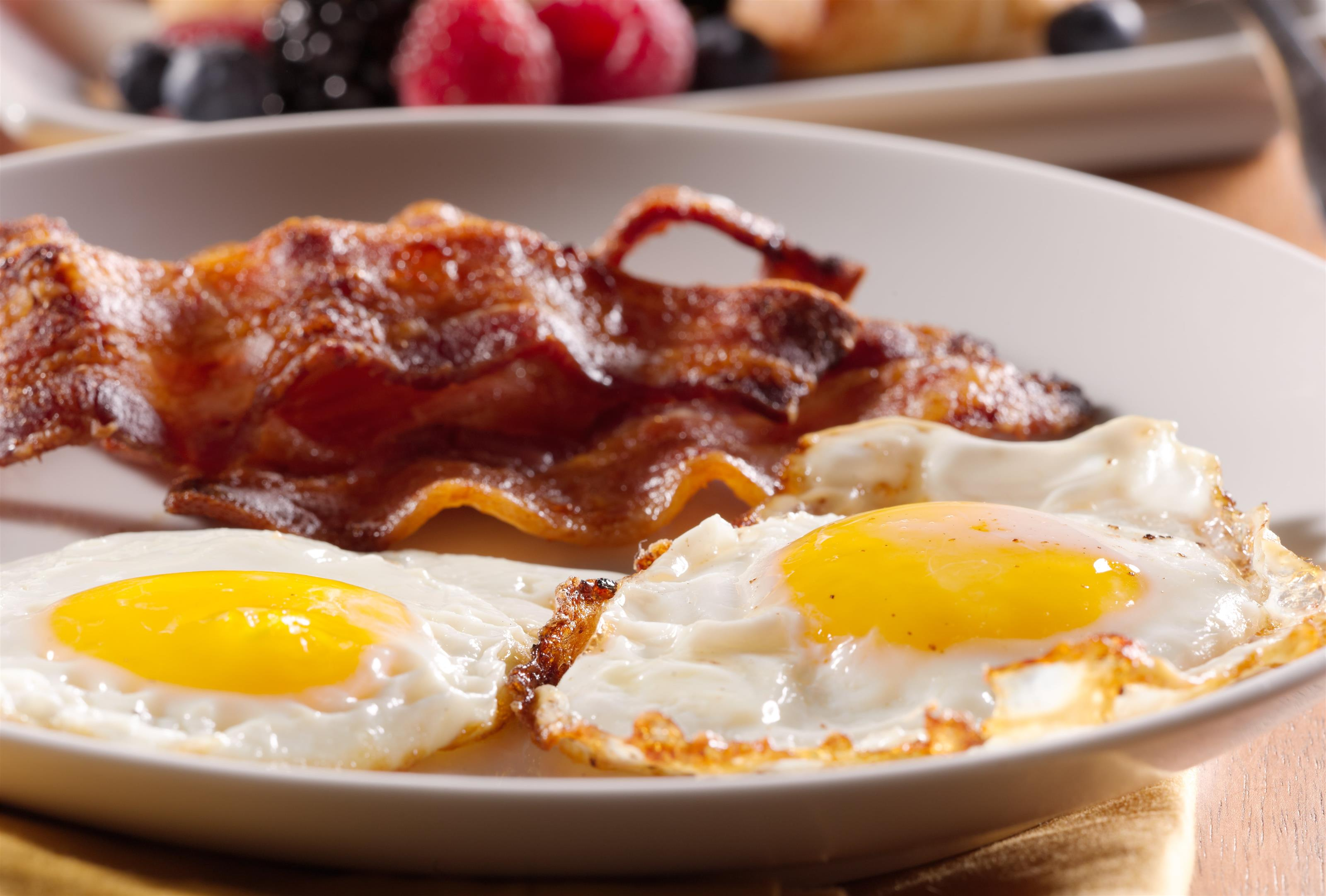 Two sunny side up eggs served with crispy bacon