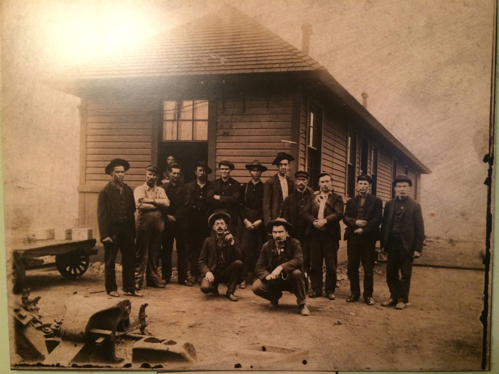 vintage photo of a group men from the early 1900's standing in front of the orchard tavern