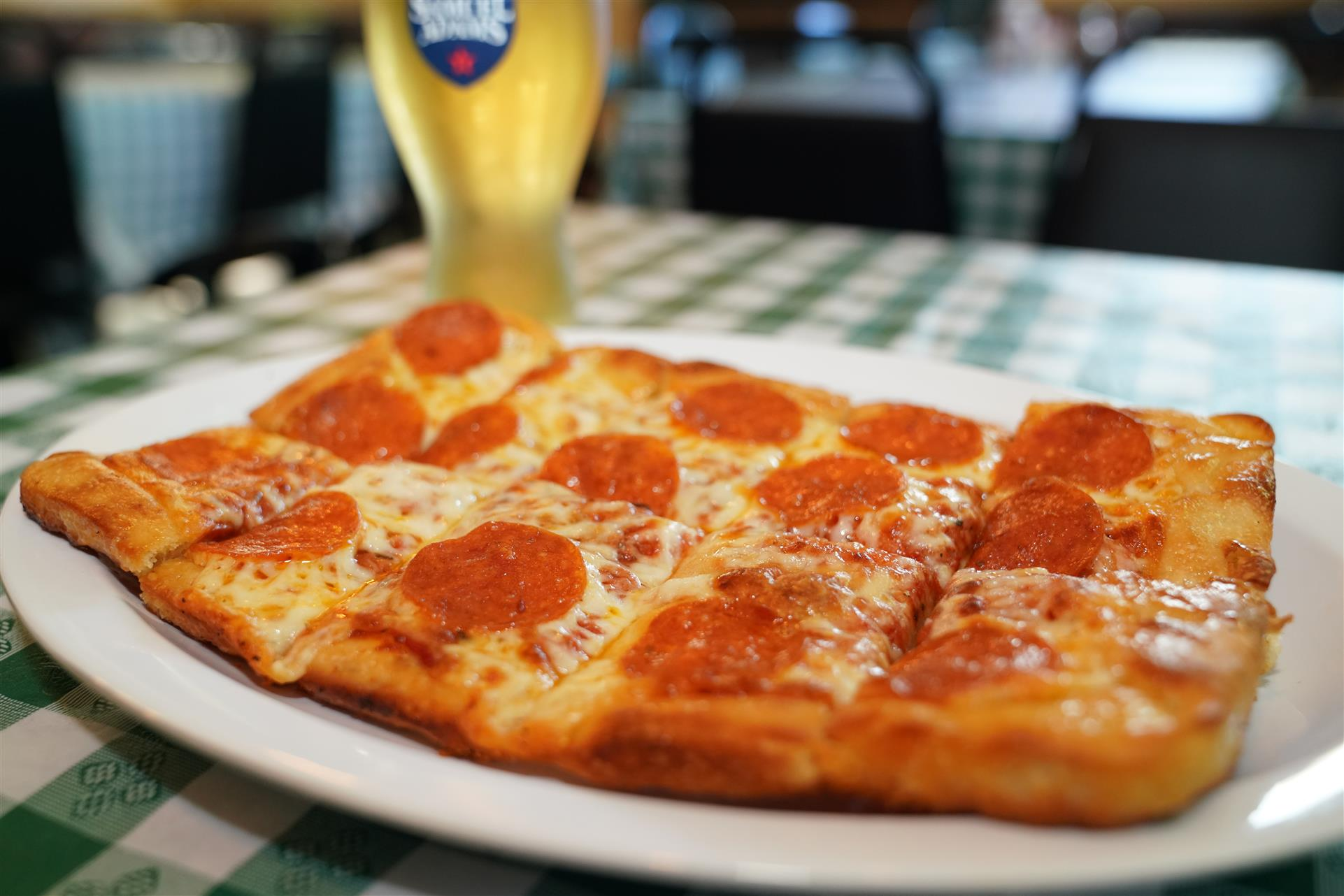 pizza with pepperoni and a beer on the side