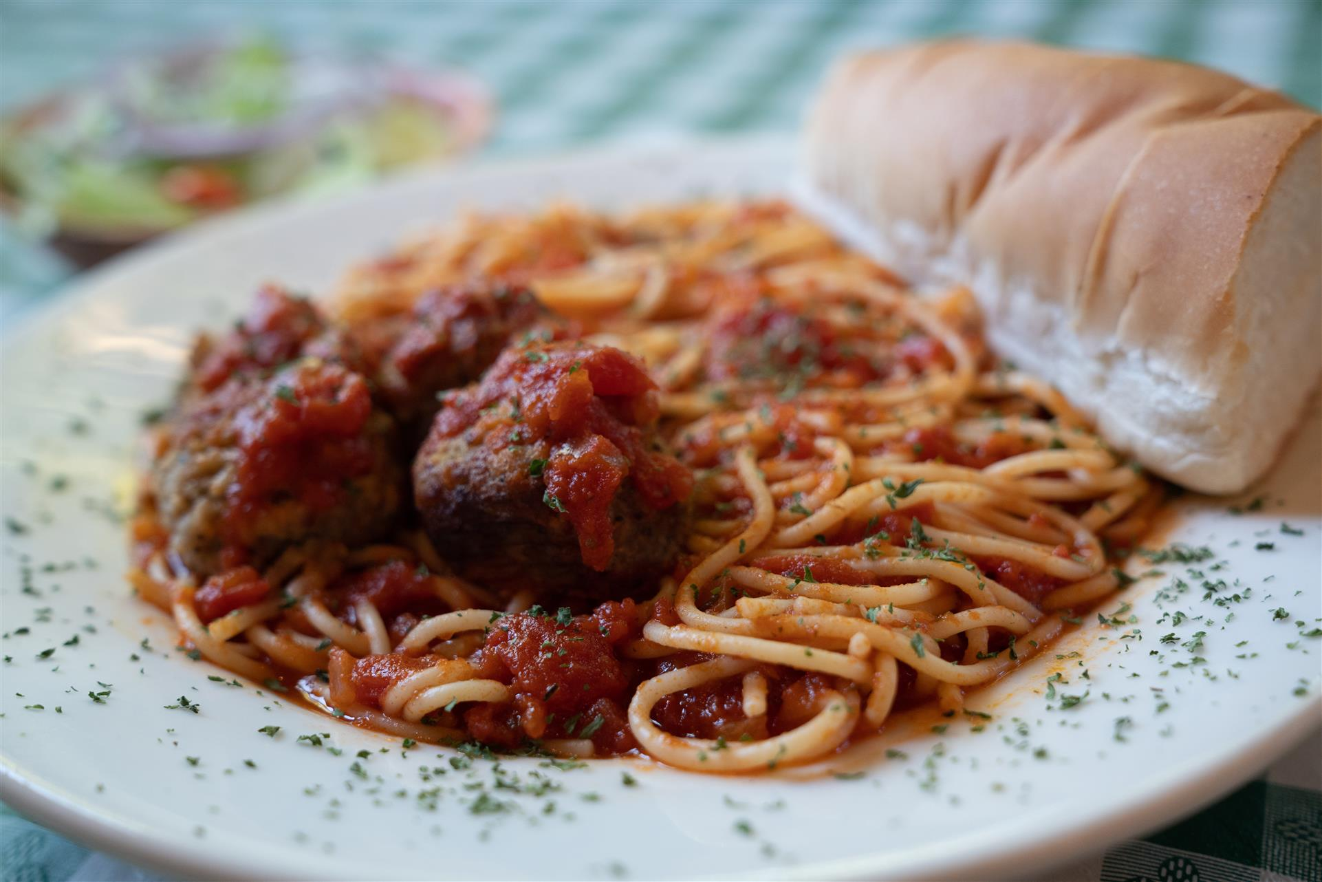 spaghetti and meatballs with a piece of bread