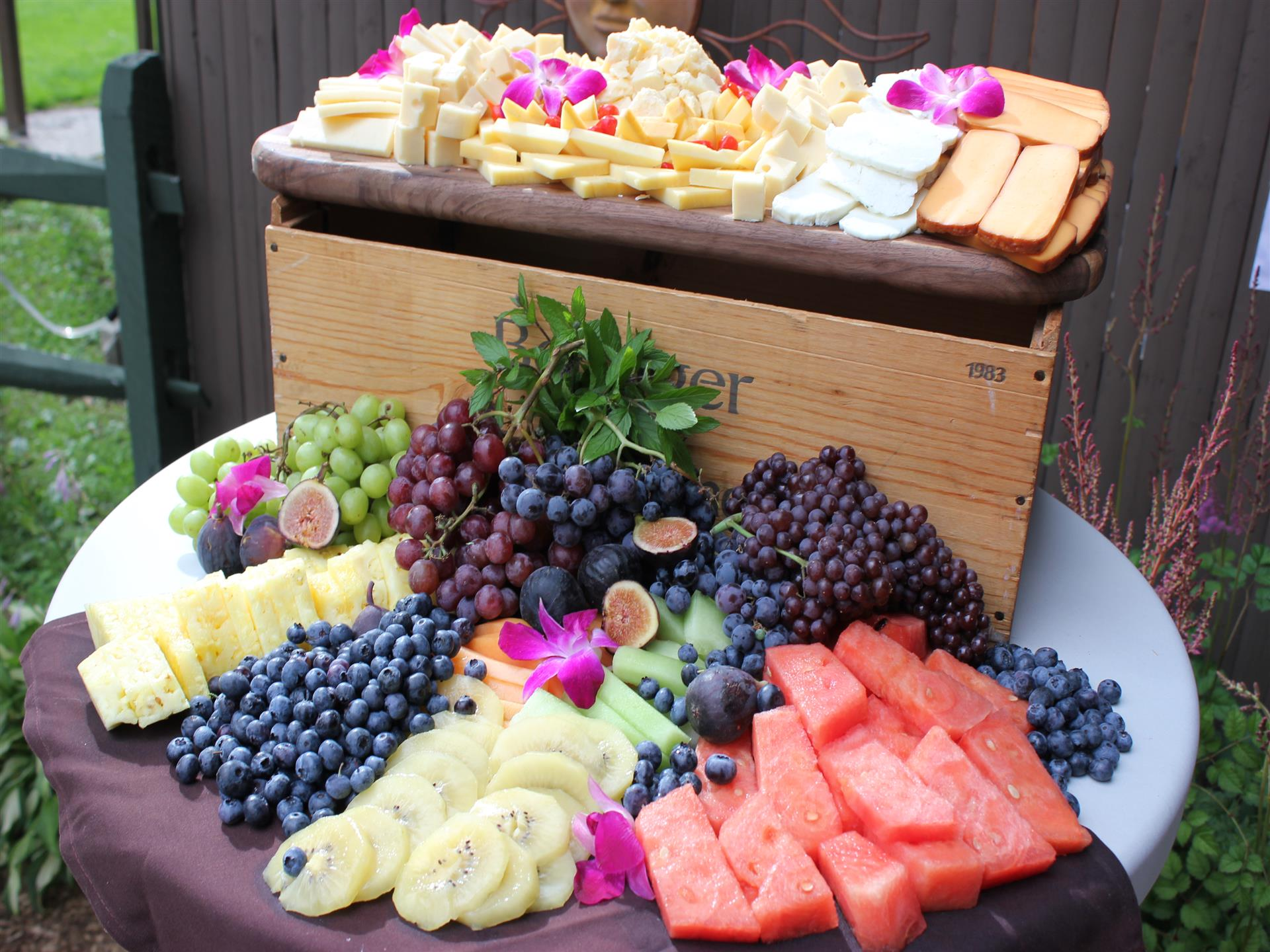 a table with assorted cheese and fruits