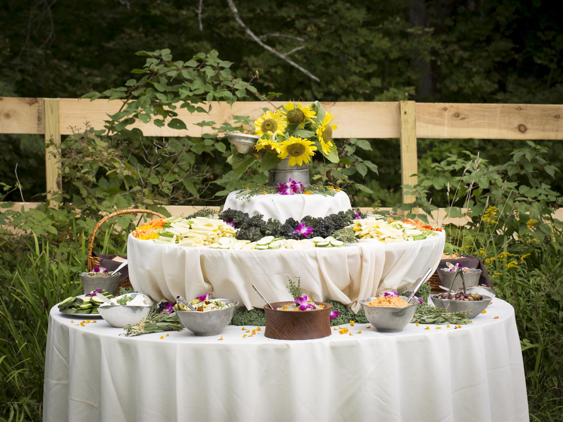 table with many different vegetables and dips with a flower bouqet of sunflowers