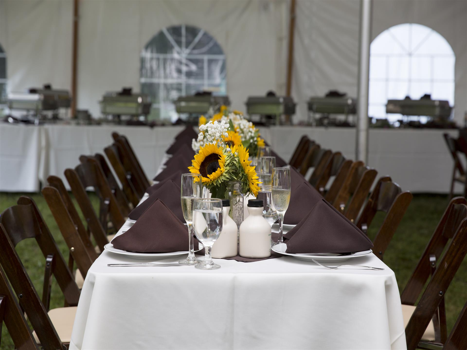 a long table with a white table cloth, wooden chairs, brown napkins, place settings and bouquets with sunflowers