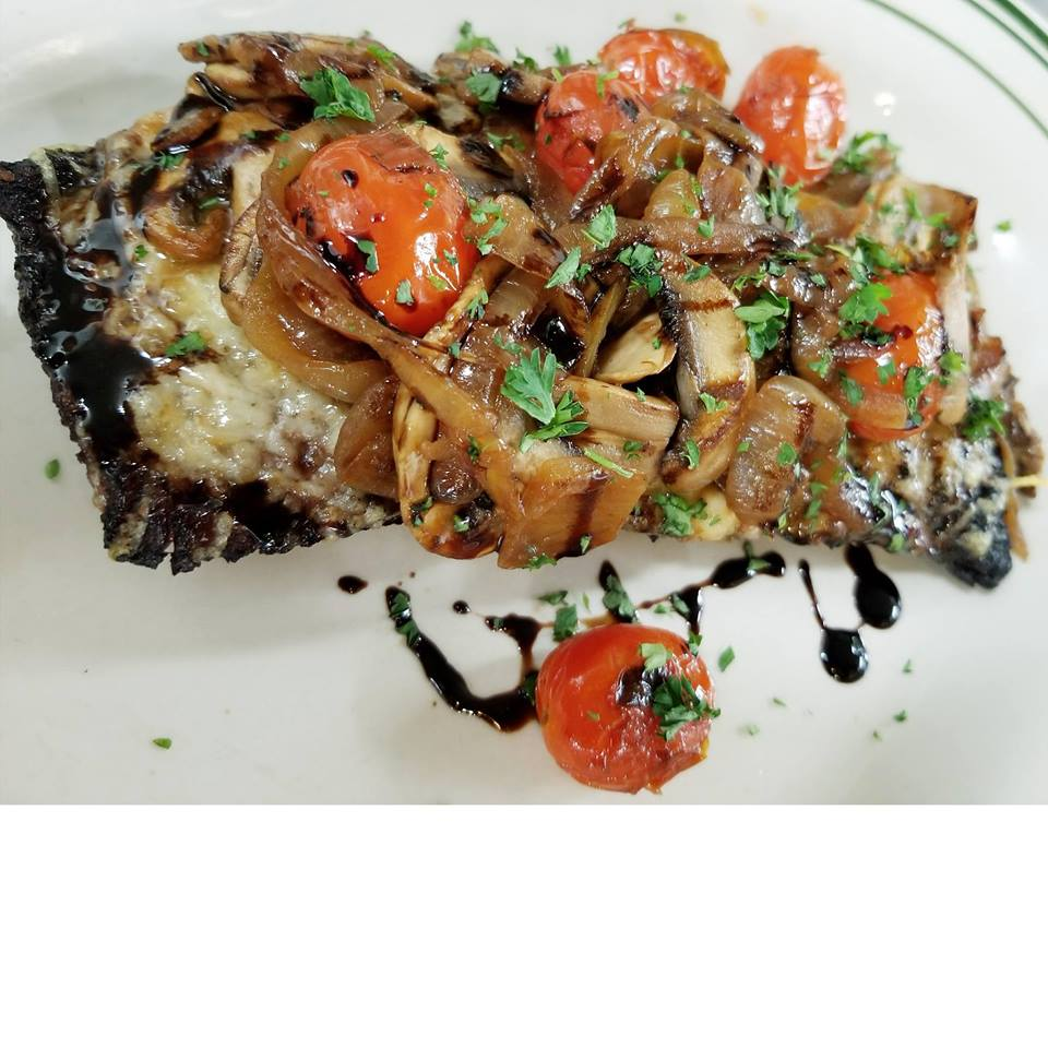 Steak topped with tomatoes and basil