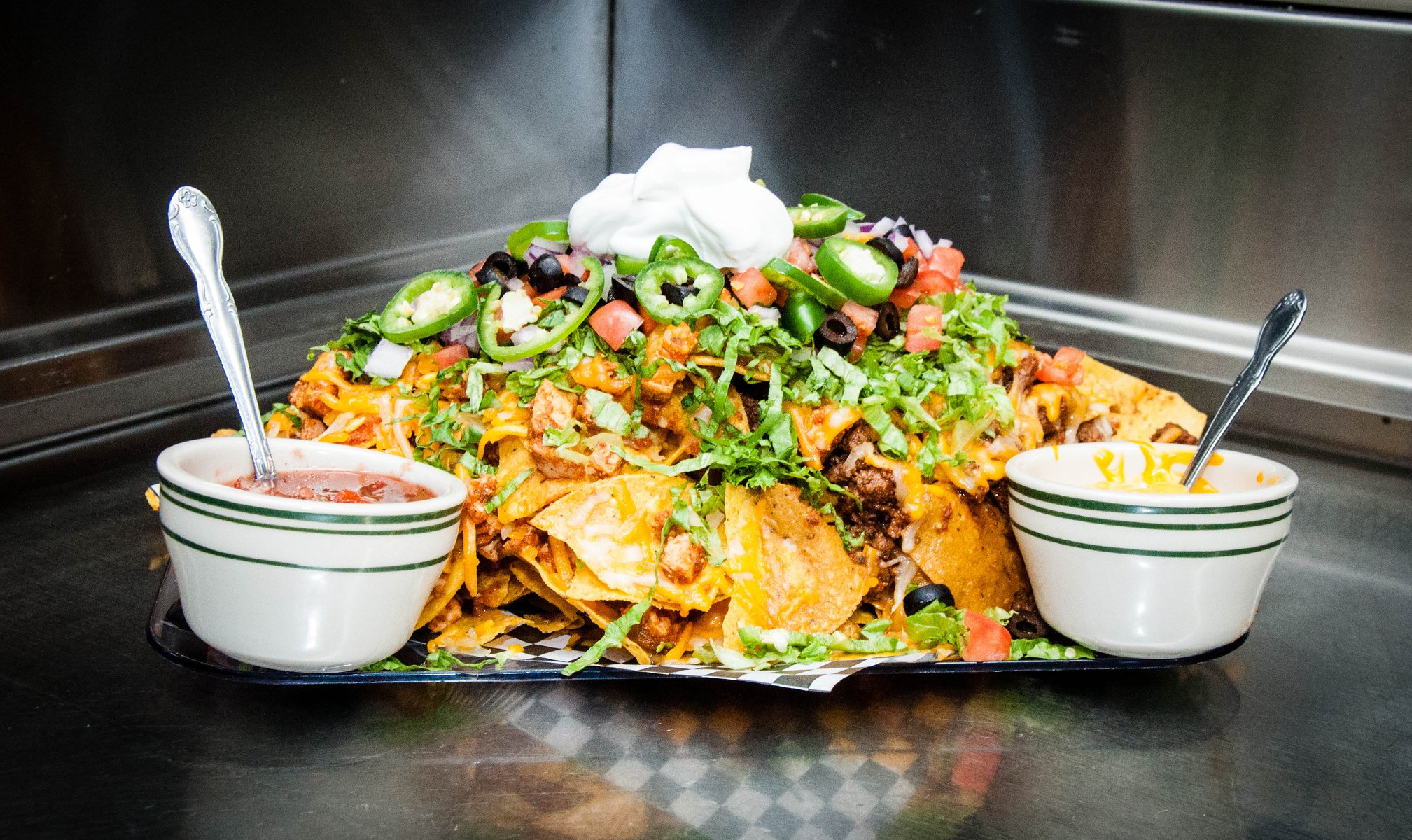 Nacho Platter with jalapenos, chopped vegetables, and dipping sauces