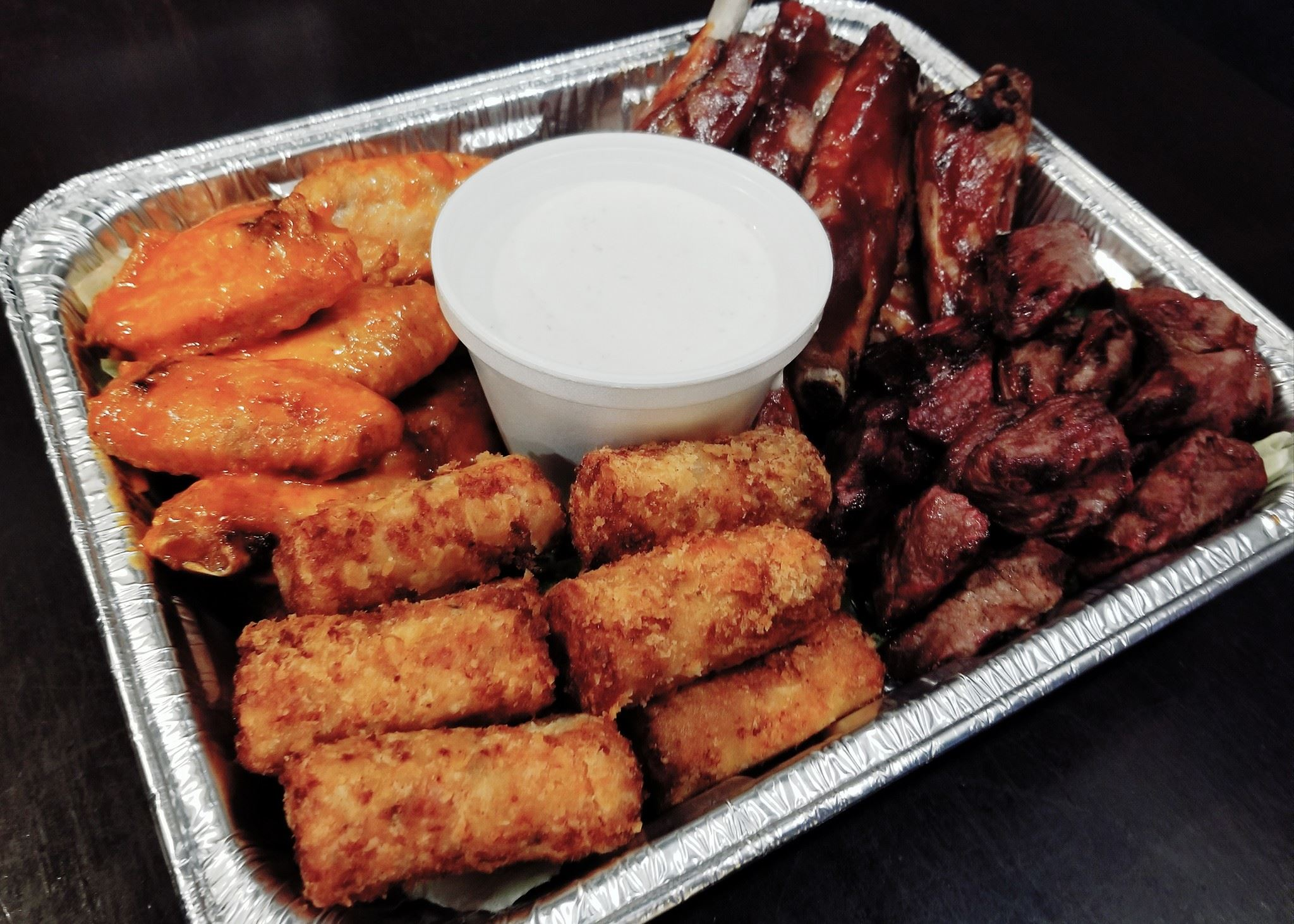 Ribs, Chicken, and other assorted meats surrounding ranch dipping sauce