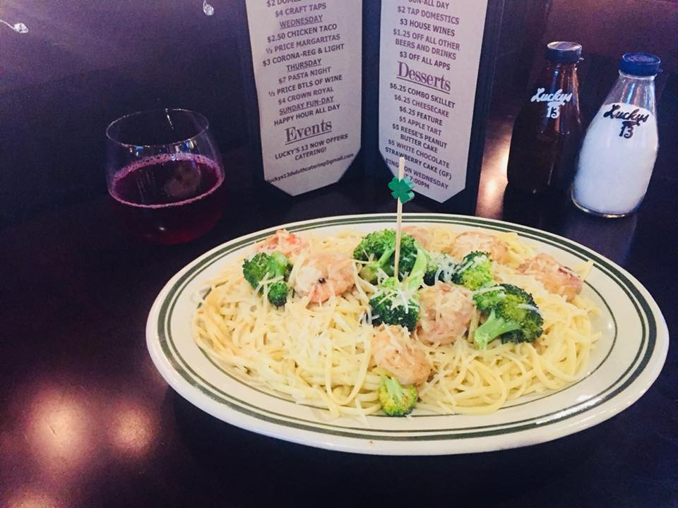 Shrimp and broccoli with bucatoni pasta in front of menu and red wine glass.