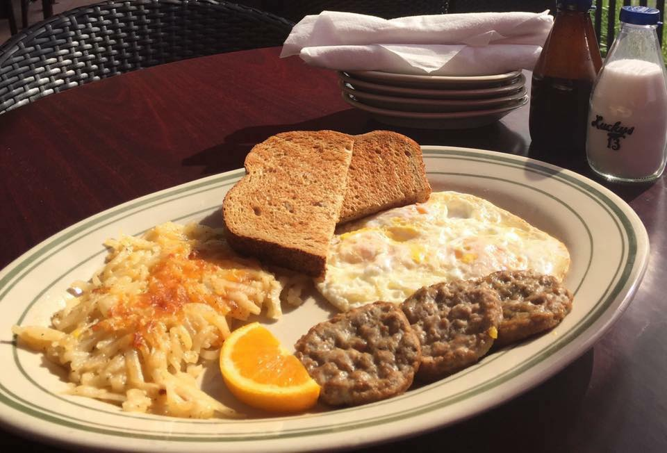 Hashbrowns, sausage patties, eggs, toast and orange slice on dish.