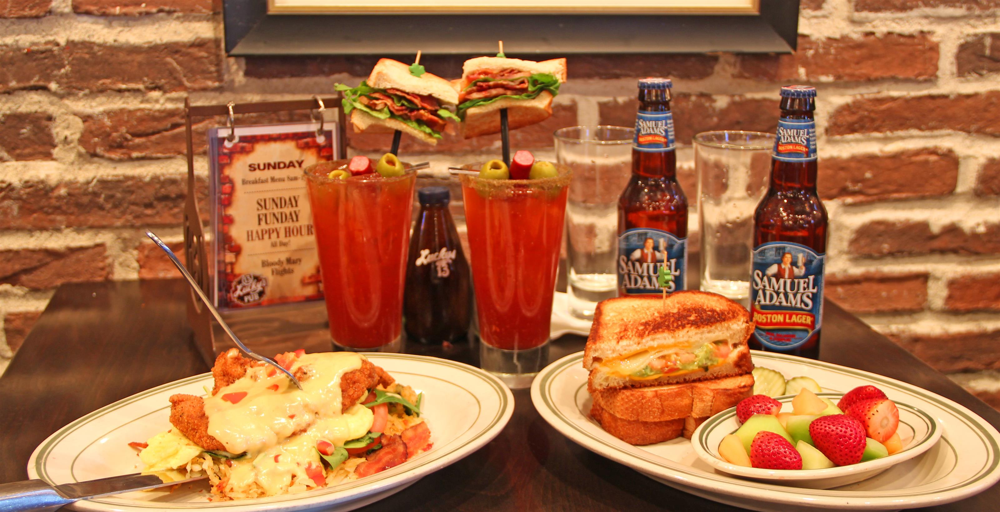 Fried fish plate next to plate with sandwich and fruit salad in front of Samuel Adams beer bottles and bloody marys.