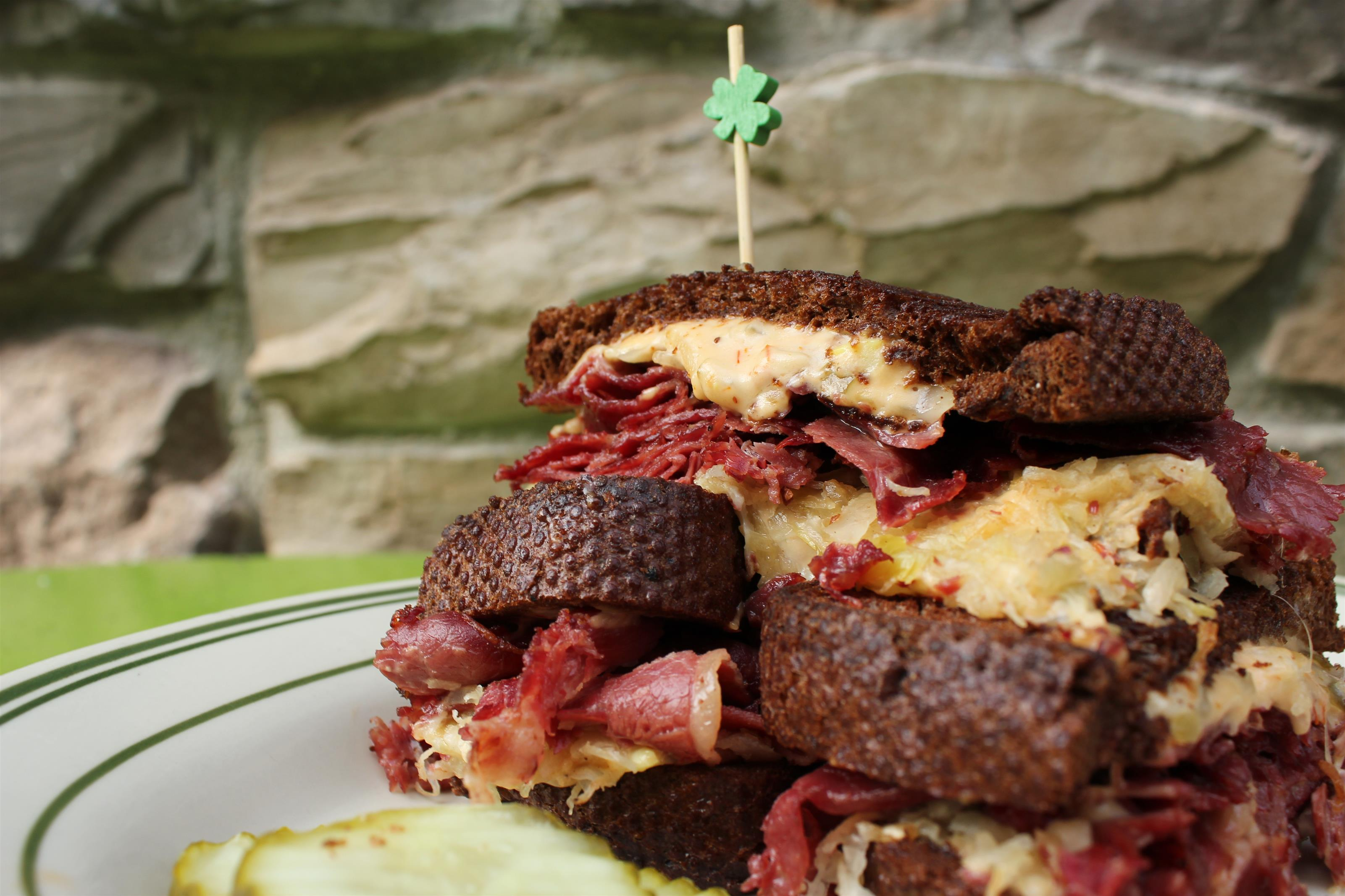Corned beef sandwich on pumpernickel with sauerkraut and mustard.
