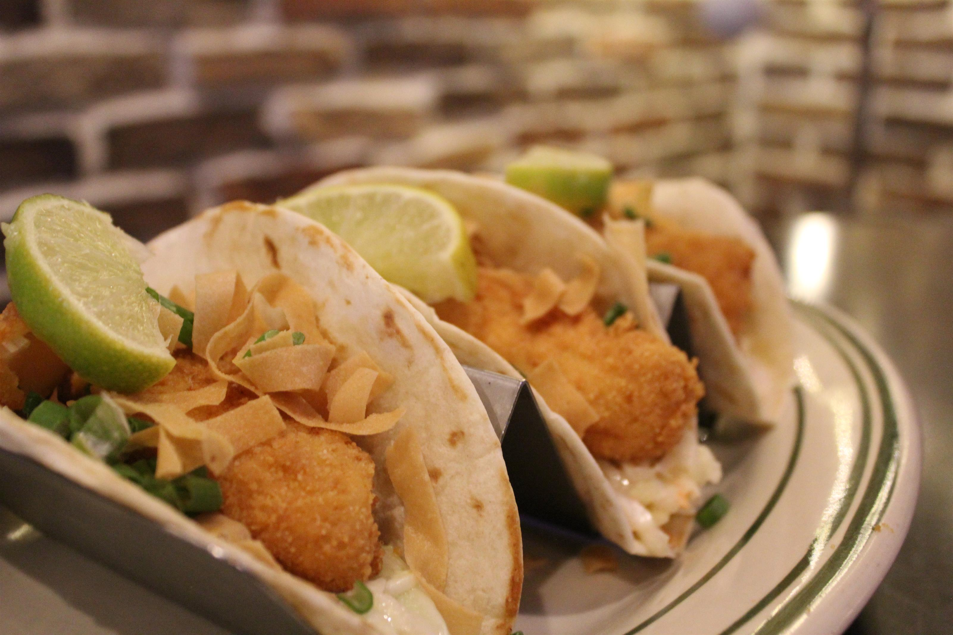 Fish tacos with tortilla strips and limes.