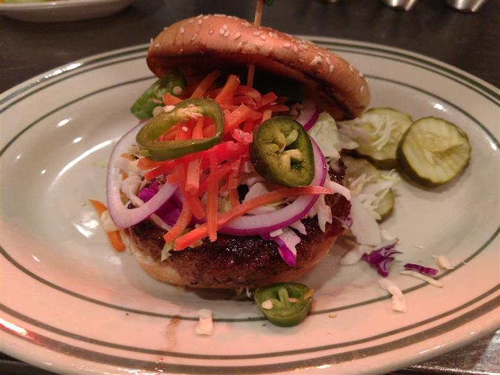 Burger served with jalapenos, onions, and sliced pickles