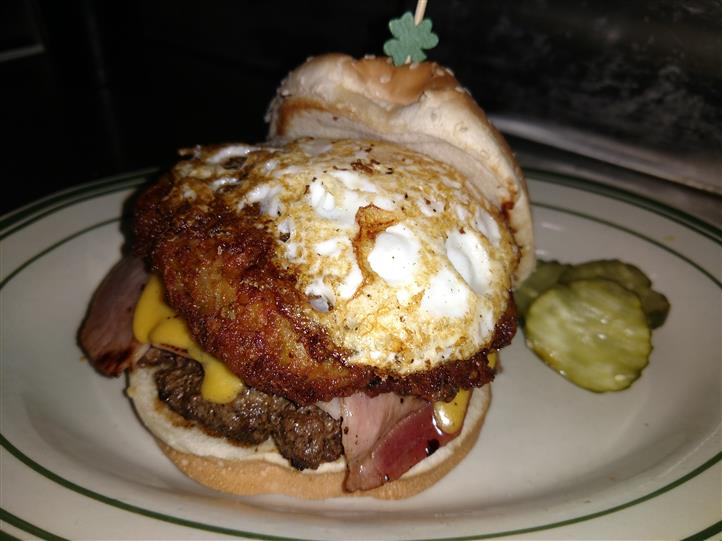 Cheese burger with eggs served with pickle slices
