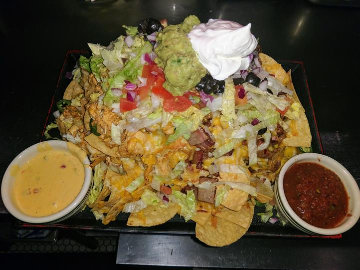 Nacho platter with steak, cheese, chopped vegetables, queso sauce, salsa, sour cream, guacamole