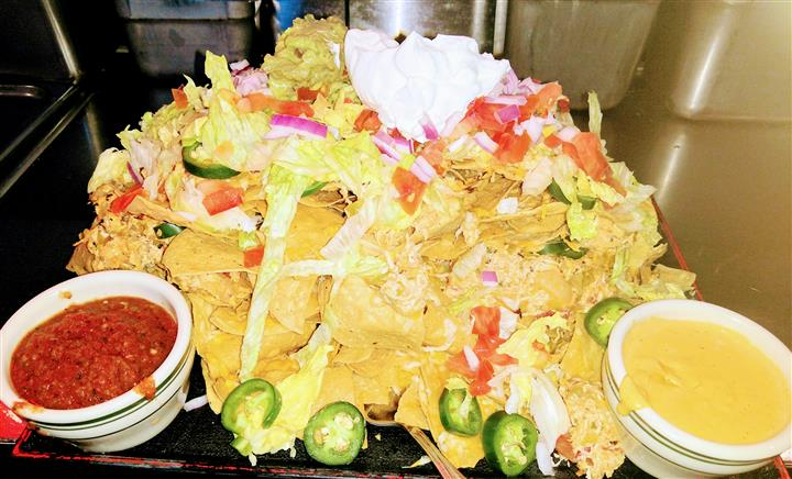 Nacho platter with jalapenos, cheese, chopped vegetables, sour cream, and salsa