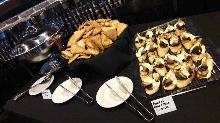 A catering table set up with roasted pear and brie crostini