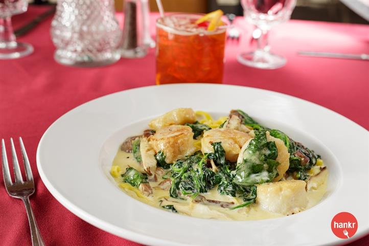 cooked scallops and spinach over sauce