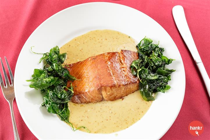 Salmon served with greens and salsa