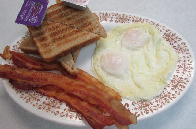 Plate of three sunny side up eggs, three slices of bacon, and toasted bread cut in half with a side of grape jelly