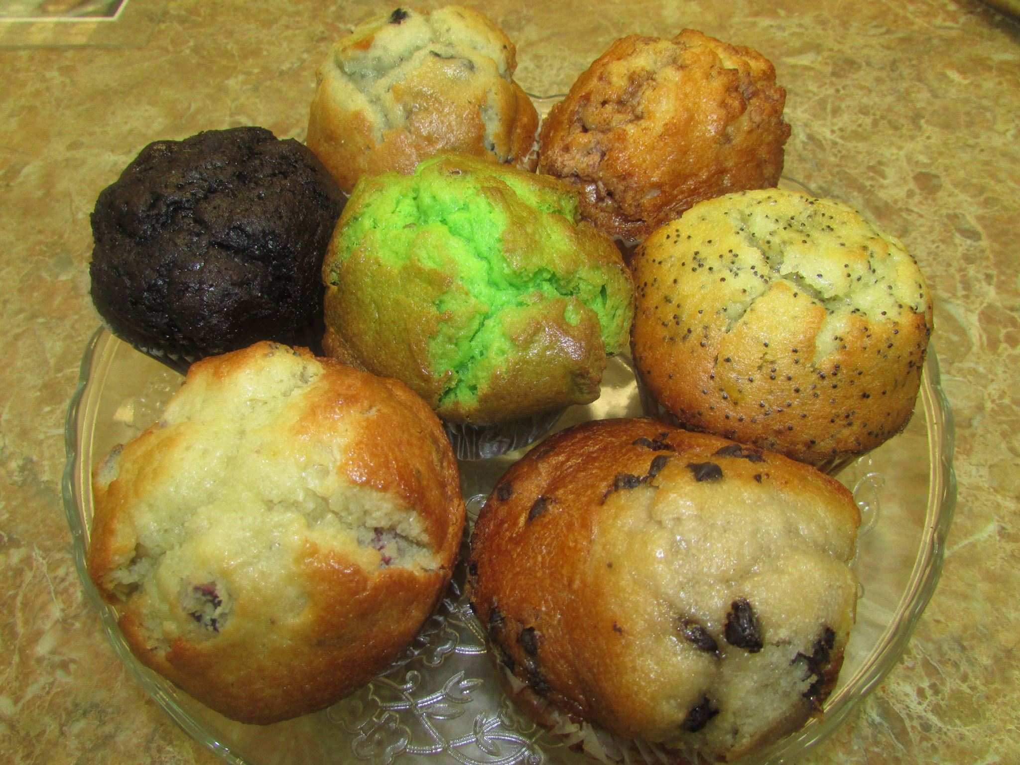 Variety of seven muffins inclusing chocolate chip, pistachio, chocolate, and poppy seed.