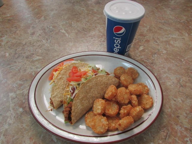 Two hard shell tacos filled with ground meat, tomatoes, shredded lettuce and cheese with a side of tater tots and a drink in a Pepsi to-go cup.
