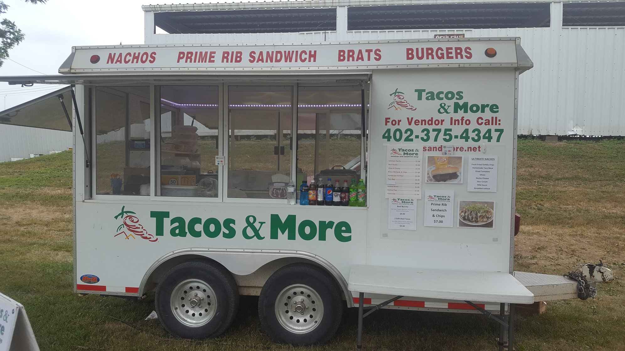 "Tacos & More Food truck with sign reading "" Nachos, Prime Rib Sandwich, Brats, Burgers"" and ""For Vendor Info Call 402-375-4347"""
