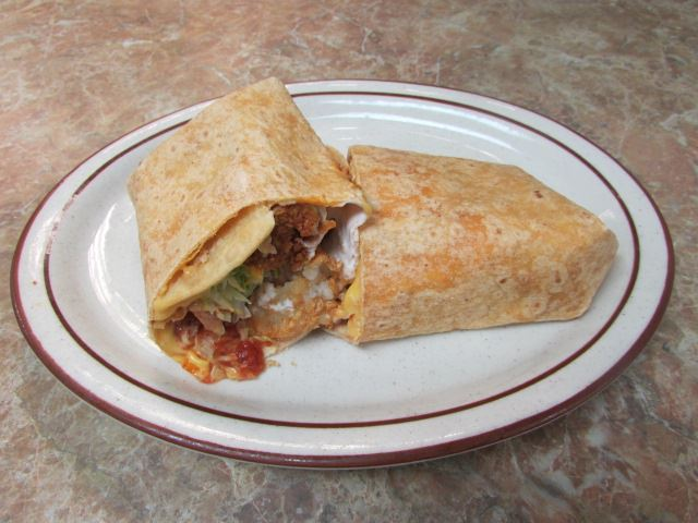 Wrap filled with ground meat lettuce, tomato, nacho cheese and sour cream