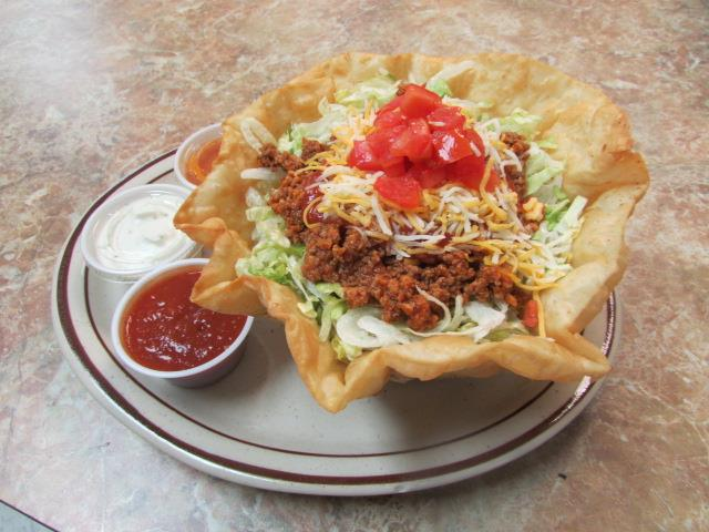 Ground seasoned beef lettuce, cheese, sauce & tomato in an edible tortilla bowl with a side of sour cream and salsa